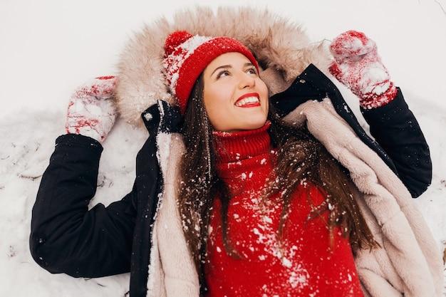 雪、暖かい服、上からの眺めの公園で横たわっている冬のコートを着て赤いミトンとニット帽の若いかなり笑顔の幸せな女性 無料写真