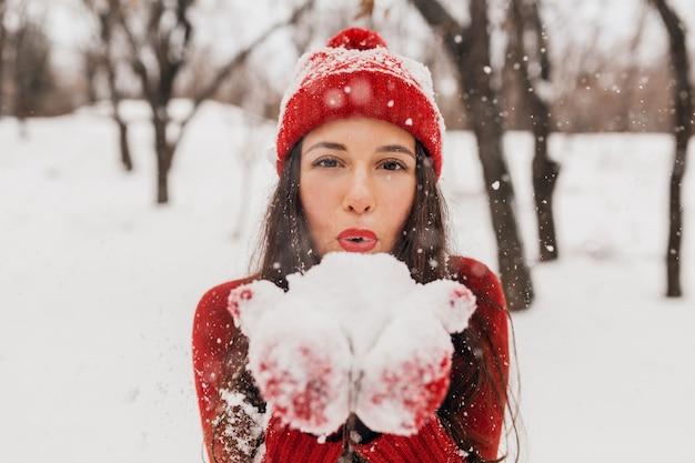 Giovane donna felice abbastanza sorridente in guanti rossi e cappello che indossa un maglione lavorato a maglia a piedi nel parco nella neve, vestiti caldi, divertendosi Foto Gratuite