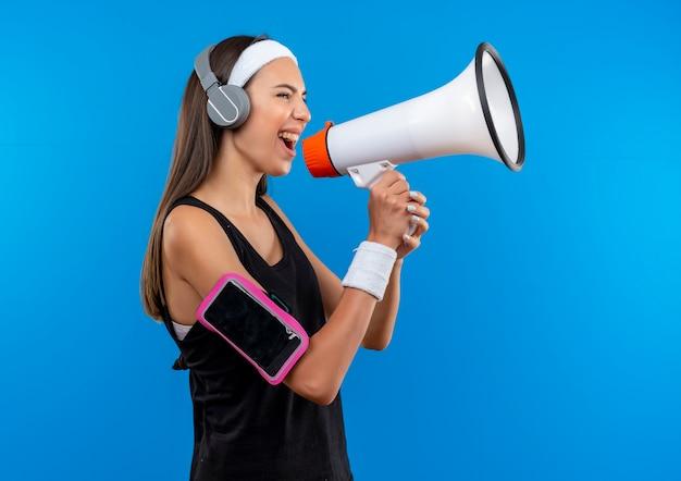 Giovane ragazza abbastanza sportiva che indossa la fascia e il braccialetto e le cuffie con la fascia del telefono che parla dall'altoparlante che sta nella vista di profilo Foto Gratuite