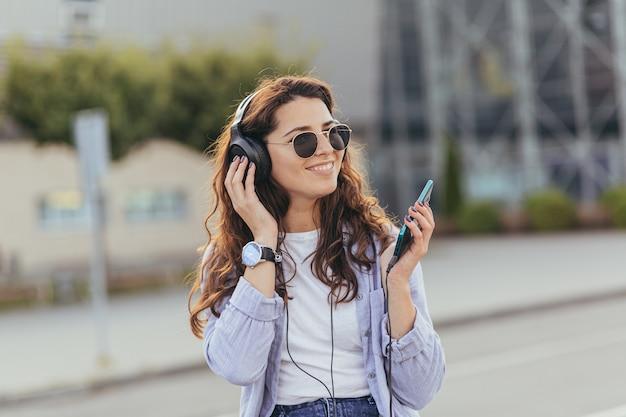 タクシーの車を待って、音楽を聴いている若いかわいい学生の女の子 Premium写真