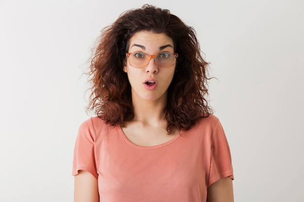 Young pretty stylish woman in glasses, curly hair, shocked, surprised face expression, funny emotion, isolated, pink t-shirt Free Photo