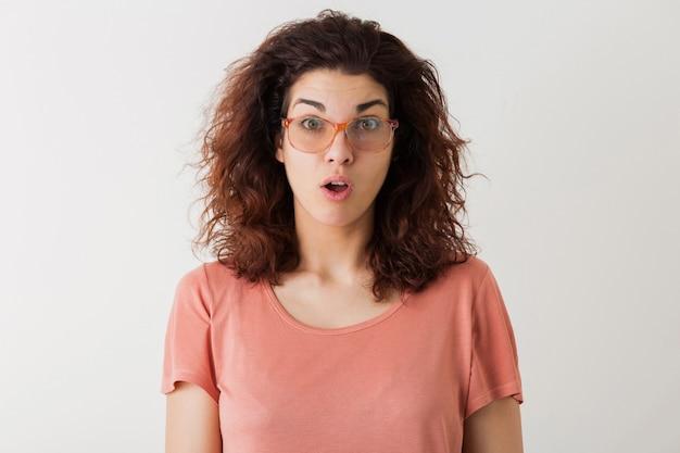 Молодая довольно стильная женщина в очках, вьющиеся волосы, шокирован, удивленное выражение лица, смешные эмоции, изолированные, розовая футболка Бесплатные Фотографии
