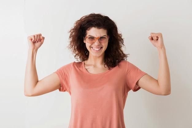 勝利のジェスチャー、強い筋肉、感情的な勝者、巻き毛、笑顔、肯定的な感情、幸せ、分離、ピンクのtシャツ、流行に敏感なスタイルで手をつないでメガネの若いかなりスタイリッシュな女性 無料写真