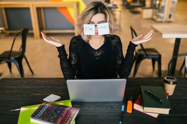 Giovane donna abbastanza stanca con adesivi di carta sui vetri che si siedono al tavolo in camicia nera che lavora al computer portatile Foto Gratuite