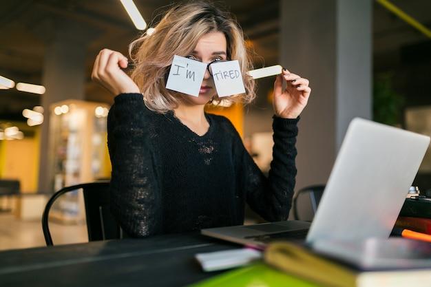 Молодая довольно усталая женщина с бумажными наклейками на очках, сидя за столом в черной рубашке, работает на ноутбуке в офисе совместной работы, смешные эмоции лица, проблемы, на рабочем месте, взявшись за руки Бесплатные Фотографии