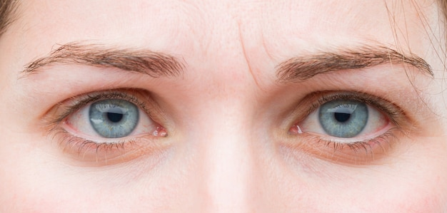 Young pretty woman blue eyes close up. sad expression Premium Photo