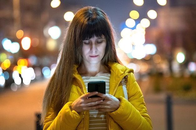屋外の夜の街の通りで彼女の携帯電話でインターネットを閲覧している若いきれいな女性。 Premium写真