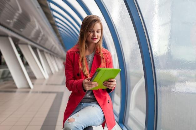 Giovane donna graziosa in abito casual tenendo il tablet portatile in edificio urbano Foto Gratuite