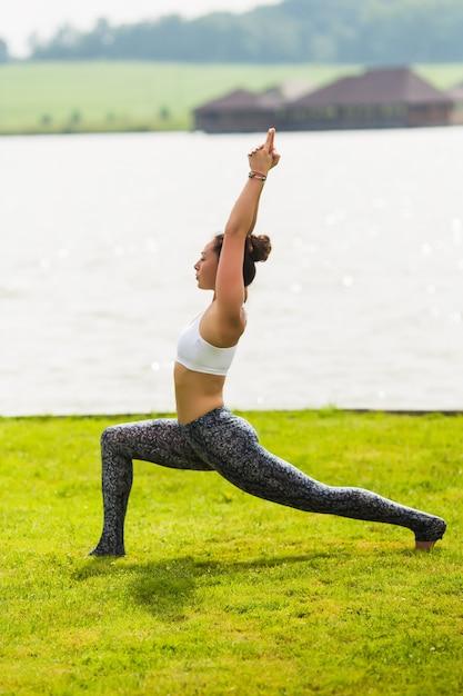 Giovane donna graziosa che fa yoga nel parco di mattina vicino al lago Foto Gratuite