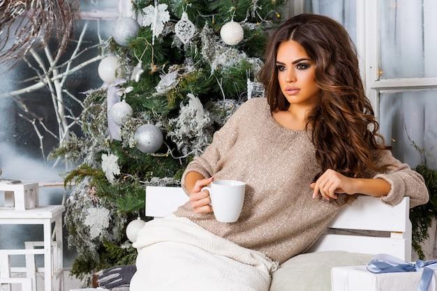 Giovane donna graziosa che beve caffè con l'albero di natale Foto Gratuite