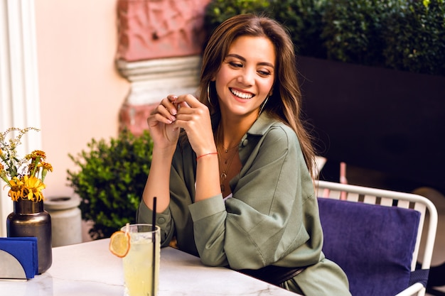 Young pretty woman drinking tasty sweet cocktail at city terrace, casual trendy outfit, weekend and travel mood. Free Photo