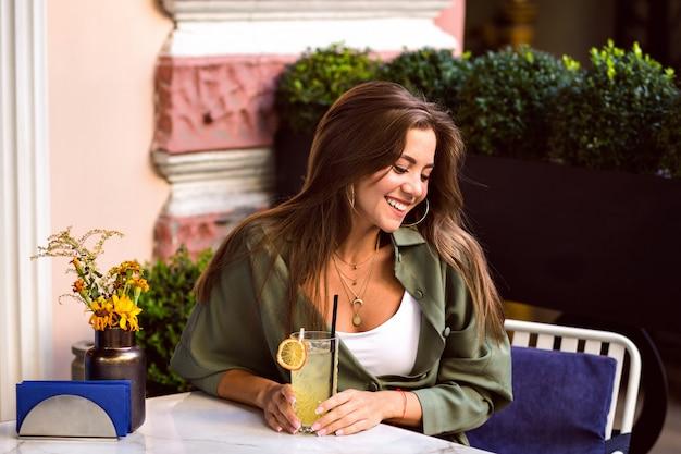 Giovane bella donna che beve gustosi cocktail dolci sulla terrazza della città, abbigliamento casual alla moda, fine settimana e atmosfera di viaggio. Foto Gratuite