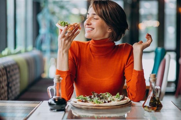 피자 바에서 피자를 먹는 젊은 예쁜 여자 무료 사진