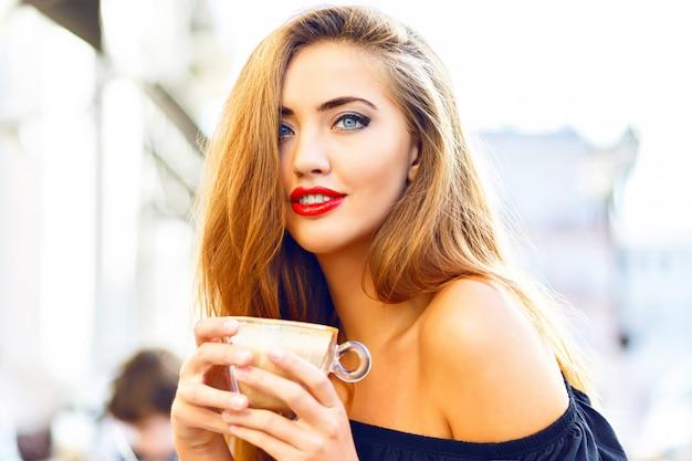 若いきれいな女性を楽しんで、カプチーノ、ラテ、朝のストリートカフェでコーヒーを飲みます。 無料写真