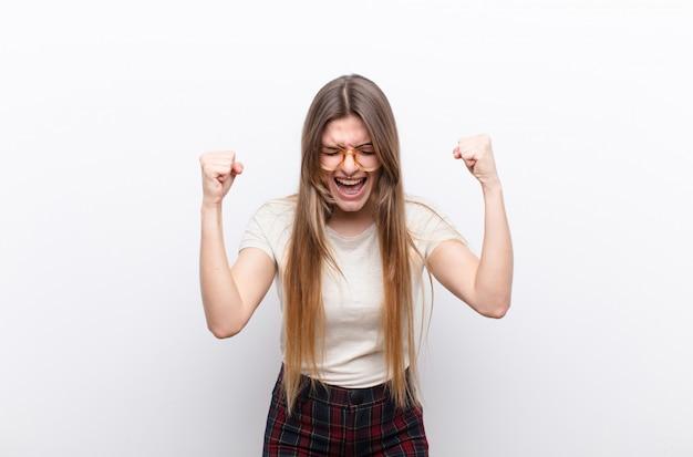 若いきれいな女性の幸せ、前向きで成功した、勝利、達成または白い壁に対する幸運を祝う Premium写真