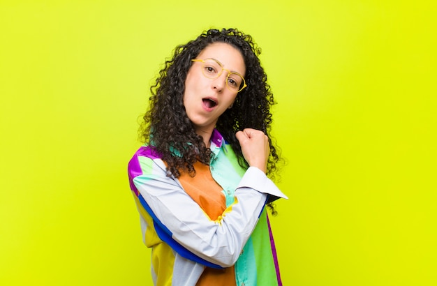 Young pretty woman feeling happy, positive and successful, motivated when facing a challenge or celebrating good results against chroma key wall Premium Photo