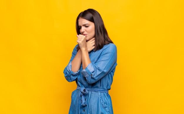 Молодая красивая женщина чувствует себя плохо с симптомами гриппа и боли в горле Premium Фотографии