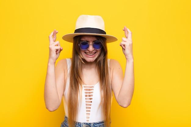 緊張して希望に満ち、指を交差させ、祈り、幸運を願って若いきれいな女性 Premium写真
