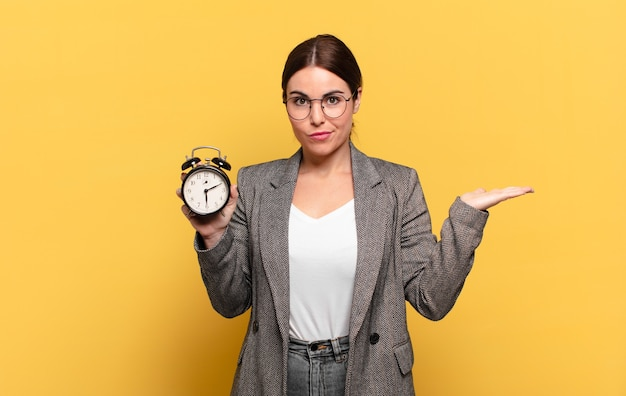 Young pretty woman feeling puzzled and confused, doubting, weighting or choosing different options with funny expression Premium Photo