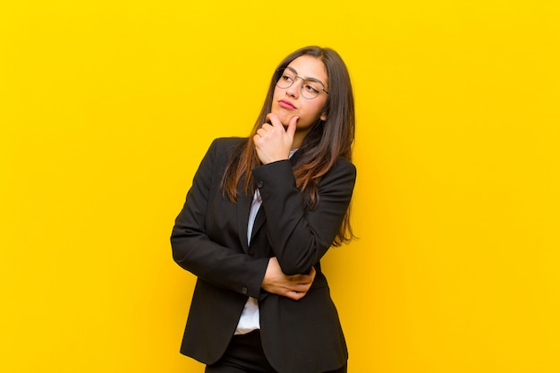 Young  pretty woman feeling thoughtful, wondering or imagining ideas, daydreaming and looking up to copyspace against orange wall Premium Photo