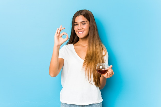 Young pretty woman holding a tea cup cheerful and confident showing ok gesture. Premium Photo