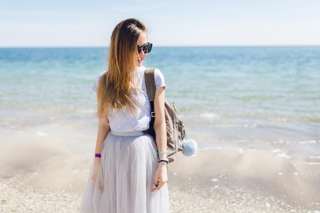 灰色のtシャツと緑豊かなスカートの若いきれいな女性が海の近くに立っています。 無料写真