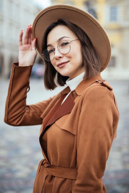 モダンなメガネとファッション帽子と茶色のコートの若いきれいな女性が市内中心部でポーズをとってください。 無料写真