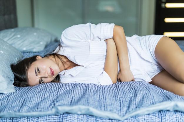 Молодая милая женщина в боли лежа на кровати Бесплатные Фотографии