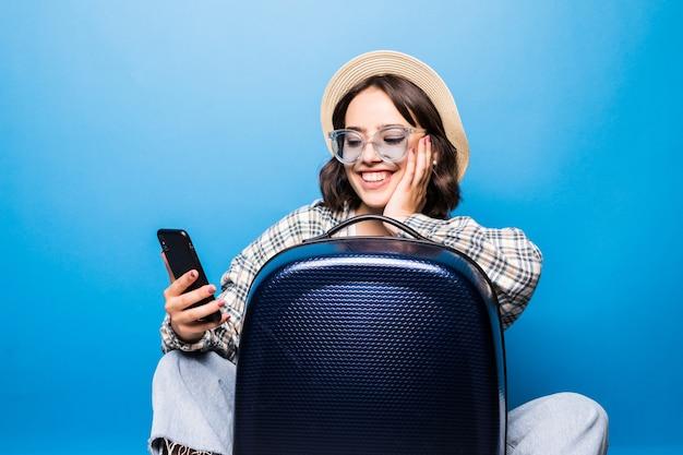 Молодая красивая женщина в солнечных очках и соломенной шляпе с чемоданом смотрит в изолированный телефон. путешествие рейсом. Бесплатные Фотографии