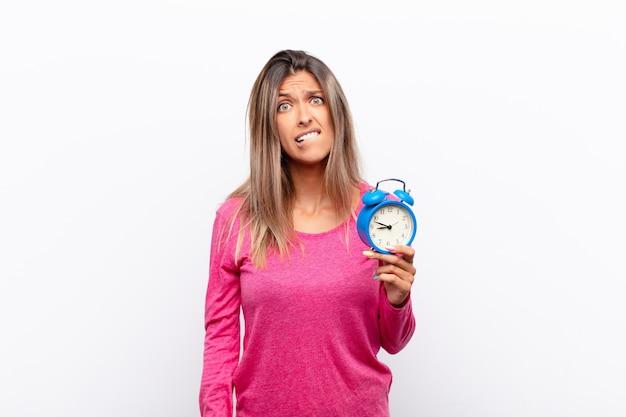 目を覚まし時計を保持している問題の答えを知らない、神経質なジェスチャーで唇を噛んで困惑し混乱している若いきれいな女性。 Premium写真
