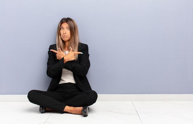 困惑し、混乱している、安全ではなく、疑問のビジネスコンセプトで反対方向を指している若いきれいな女性 Premium写真