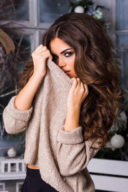 Giovane donna graziosa che posa con la maglia di scintillio Foto Gratuite