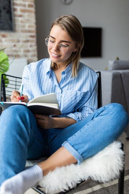 Молодая красивая женщина читает или замечает книгу и сидит на удобном стуле дома Premium Фотографии