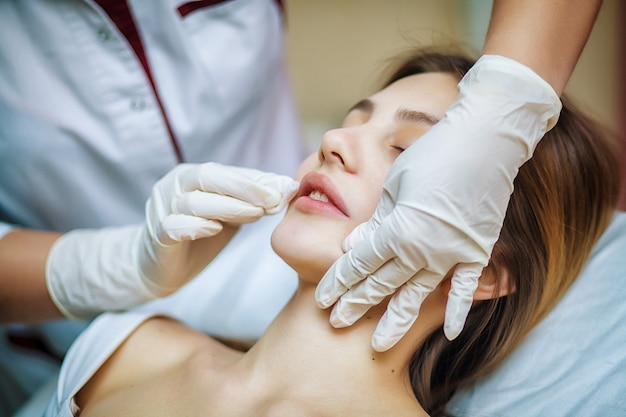 ビューティーサロンで治療を受ける若いきれいな女性。ソファに横になっているオフィスの美容師の若い美しい女性。輪郭を描く手順、活性化。美容注射。 Premium写真