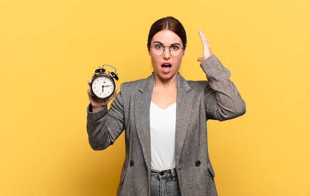 Young pretty woman screaming with hands up in the air, feeling furious, frustrated, stressed and upset Premium Photo