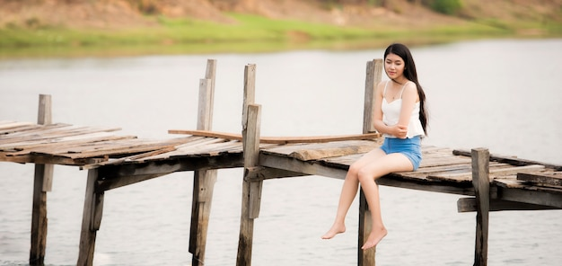 Young pretty woman sitting alone on the pier Premium Photo