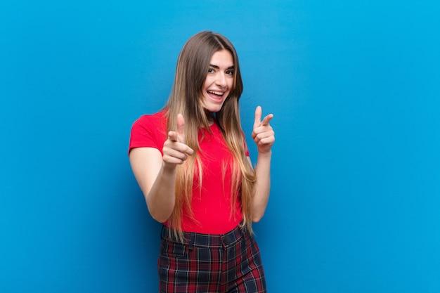陽気な成功した、幸せな態度を指して、青い壁に手で銃のサインを作って笑顔若いきれいな女性 Premium写真