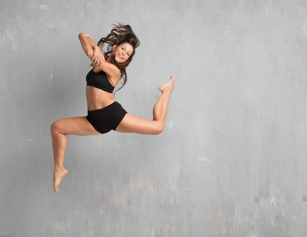Young pretty woman street dancer jumping against grunge wall bac Premium Photo