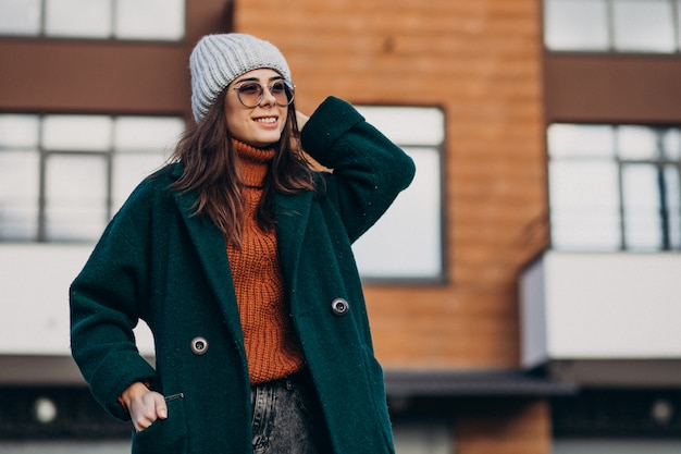 Young pretty woman in warm coat by the house Free Photo