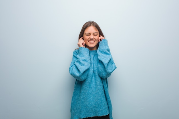 Young pretty woman wearing a blue sweater covering ears with hands Premium Photo