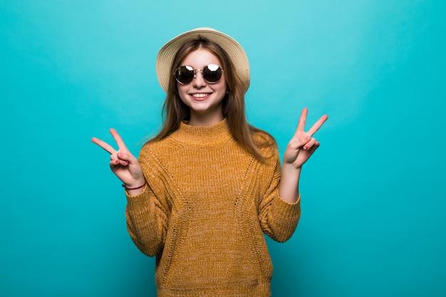 La giovane donna graziosa che indossa in cappello e occhiali da sole ha indicato il gesto di pace sulla parete blu Foto Gratuite