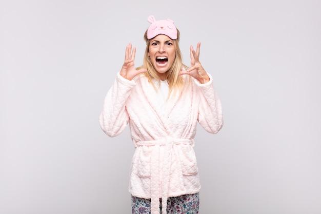 Молодая красивая женщина в пижаме, кричащая с поднятыми руками, чувствуя ярость, разочарование, стресс и расстройство Premium Фотографии