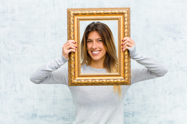 Young pretty woman with a baroque frame against grunge wall Premium Photo