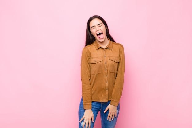 陽気な、屈託のない、反抗的な態度、冗談と舌を突き出し、ピンクの壁を越えて楽しんで若いきれいな女性 Premium写真