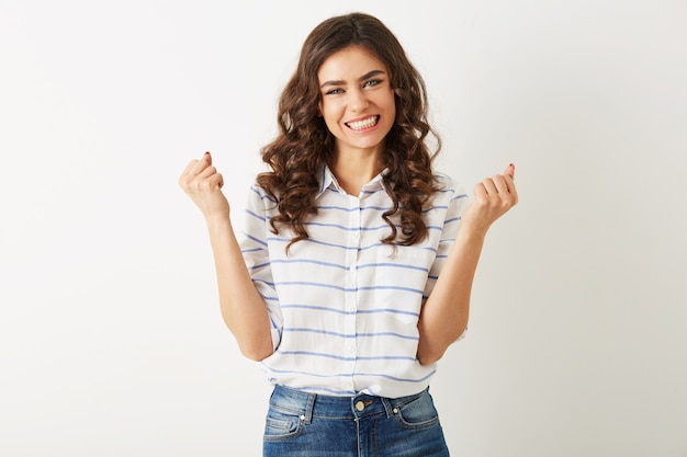 Young pretty woman with emotional face expression, holding hands up, success, winner, casual style, isolated, happy, positive mood, sincere smile, long curly hair, white teeth, strong, independed Free Photo
