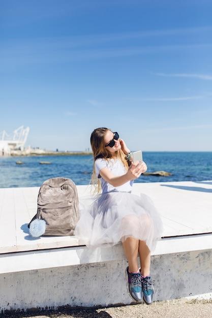 Giovane bella donna con i capelli lunghi è seduta sul molo Foto Gratuite