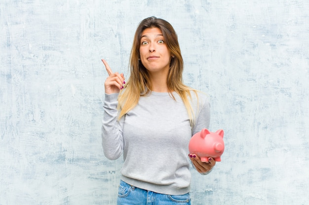 Young pretty woman with a piggy bank against grunge wall Premium Photo