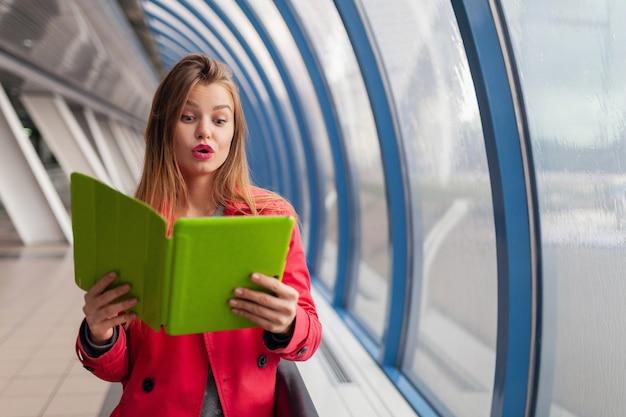 Giovane donna graziosa con l'espansione del viso sorpreso che tiene il portatile della compressa in edificio urbano Foto Gratuite