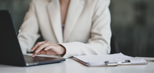 Young professional businesswoman working on her project while typing on laptop Premium Photo