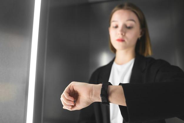 엘리베이터에서 그녀의 시계를 확인하는 젊은 전문가. 프리미엄 사진